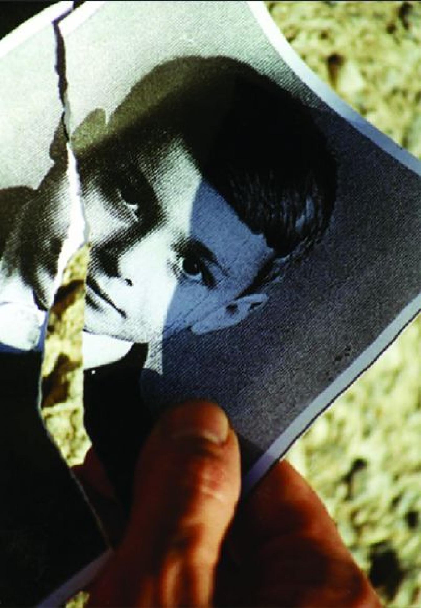 Fotografia małego, około dziesięcioletniego chłopca. Fotografia jest czarno-biała i przetargana w połowie. Fotografie ktoś trzyma w dłoni.