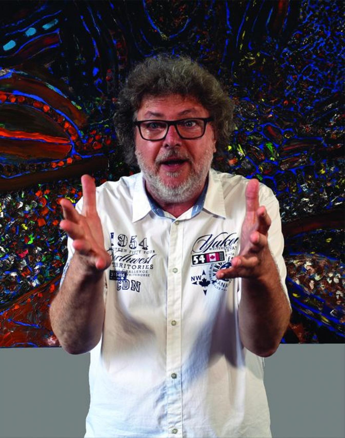 Zdjęcie starszego mężczyzny. Nosi okulary, brodę. Ubrany jest w białą koszulę z krótkim rękawem. Żywiołowo gestykuluje dłońmi.