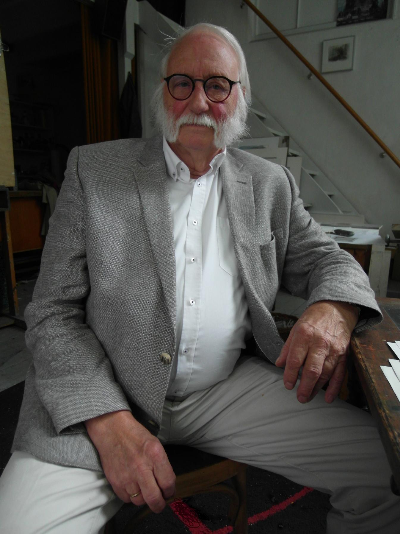 Portret Jana Wagnera. Starszy mężczyzna z siwymi włosami oraz brodą. Ubrany w szarą marynarkę i spodnie oraz białą koszulę. Siedzi na krześle w swoim mieszkaniu.